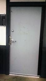 The nondescript and dirty entrance door.